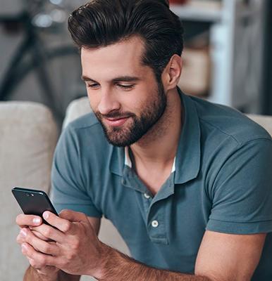 Homem segurando um celular sentado num sofá